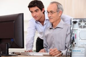 Young Computer Technician Helping Older Man