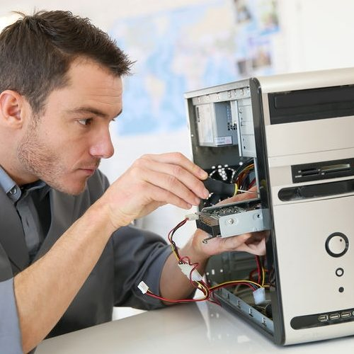 A Picture of a Technician Fixing Computer.